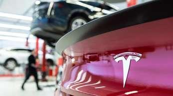 Das Logo des Fahrzeugherstellers Tesla auf einem Fahrzeug in einem Tesla Service Center.