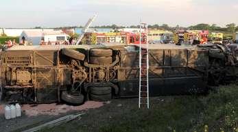 Einsatzkräfte der Feuerwehr stehen an der Unfallstelle neben dem verunglückten Bus. Der Bus überschlug sich zwischen den Anschlussstellen Leipzig-West und Bad Dürrenberg. Anschließend blieb das Fahrzeug auf der Seite liegen.