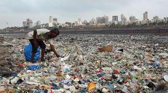 Ein Mann sammelt Plastik an der von Müll übersäten Küste des Arabisches Meeres in Mumbai.