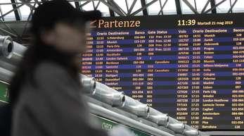 Ein Passagier steht vor einer Fluginformationstafel am Flughafen Rom-Fiumicino.