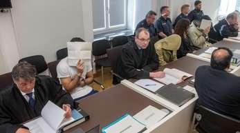Die Angeklagten sitzen neben ihren Anwälten im Verhandlungssaal des Amberger Amtsgerichts.