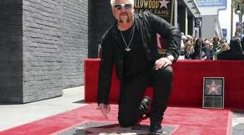 Der Star-Koch und TV-Show-Moderator Guy Fieri kniet neben seinem Stern auf dem «Walk of Fame».
