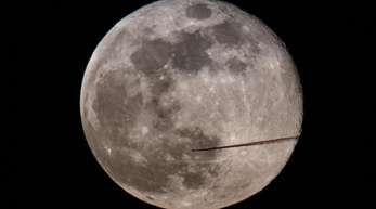 Ein Flugzeug fliegt am Abend am Vollmond vorbei.