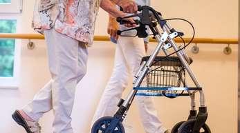 Eine Pflegekraft geht in einem Pflegeheim mit einer älteren Dame über einen Korridor. Künftig sollen Beschäftige in der Alten- und Krankenpflege besser bezahlt werden.