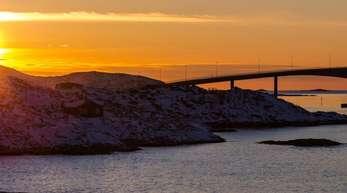Die Sonne geht hinter der Sommaroy-Brücke unter, die die Inseln Kvaloya und Sommaroy verbindet.