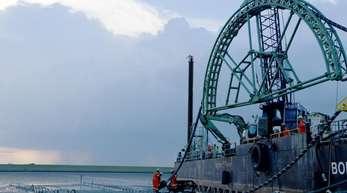 Das Endstück eines 516 Kilometer langen Seekabels wird vom Kabelverlegeschiff «Boka Connector» im Watt unter dem Deich hindurch an Land gezogen.