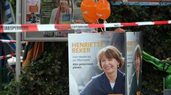 Plakate der damaligen Kölner Oberbürgermeister-Kandidatin Henriette Reker hinter Absperrbändern der Polizei am Tatort.