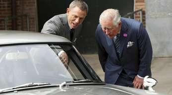 Daniel Craig (l) zeigt Prinz Charles (r) den Aston Martin DB5.