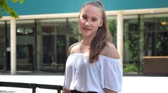Niedersachsens jüngste Abiturientin Mandy Hoffmann steht mit einem Blumenstrauss in der Hand vor ihrer Schule. Mandy hat mit 14 Jahren das Abitur mit der Note 1,0 bestanden.
