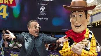 """Tom Hanks (l) neben Woody auf dem Roten Teppich bei der Premiere des Films """"Toy Story 4"""" in London."""