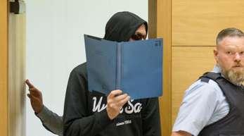 Einer der beiden Angeklagte betritt den Sitzungssaal im Landgericht Bielefeld.