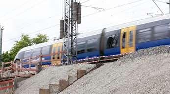 Ein Zug fährt bei Osnabrück über eine alte Brücke, die mit Stahlbetonelementen erneuert wird.