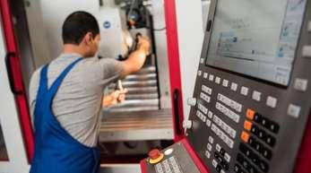 Ein Auszubildender, der 2012 aus dem Iran nach Deutschland geflohen war, setzt ein Werkzeug in eine Fräsmaschine ein. Betriebe in Deutschland bilden immer mehr Flüchtlinge aus.