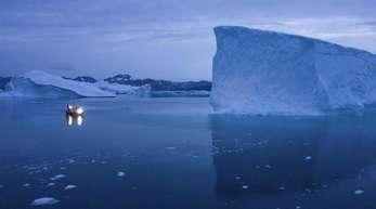Ein Boot umfährt in der Dämmerung einen Eisberg auf Grönland.