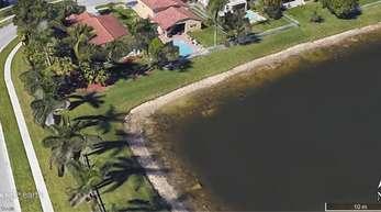 Satellitenaufnahme von Google Earth: Etwa in der Bildmitte, nahe am Ufer des kleinen Sees, ist das verrottete Autowrack zu sehen.
