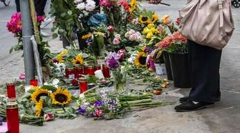 Eine Frau legt Blumen an der Stelle ab, an der vier Menschen bei einem Verkehrsunfall ihr Leben verloren hatten.