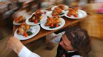 Diät geht anders: Kellner auf dem Oktoberfest mit einem Tablett Hendl (Hähnchen).