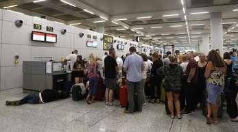 Gestrandete Urlauber stehen in einer Schlange am Flughafen von Palma de Mallorca.