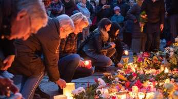 Trauernde legen an der Mauer der Synagoge Blumen nieder und zünden Kerzen an.
