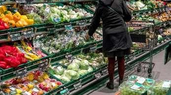 In den Regalen eines Supermarkts liegen Obst und Gemüse.