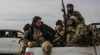 Mitglieder der von der Türkei unterstützten Syrischen Nationalarmee sitzen auf Fahrzeugen. Die Soldaten versammeln sich nahe der türkisch-syrischen Grenze, um das türkische Militär zu unterstützen, das seine Offensive gegen Kurdenmilizen in Nordsyri