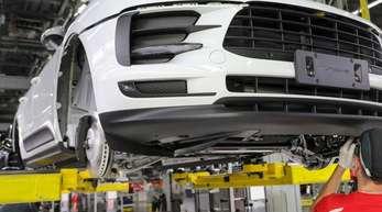 Ein Mitarbeiter arbeitet in der Montage an einem Porsche Macan im Werk Leipzig.