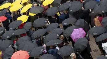 Mit Regenschirmen beteiligen sich zahlreiche Menschen auf der Buchmesse an einer Mahnwache für die Meinungsfreiheit.