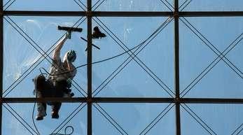 Ein spezialisierter Glas- und Gebäudereiniger putzt in 27 Metern Höhe ein Dach.