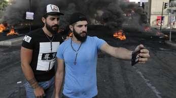 Zwei Teilnehmer einer Demonstration fotografieren sich vor einer brennenden Straßenblockade mit einem Smartphone.