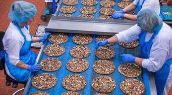 Mitarbeiterinnen belegen im Pizzawerk der Firma Dr. Oetker kakaohaltige Pizzaböden mit Schokoladensplittern. Die Schokoladenpizza wird nach zwei Jahren eingestellt.