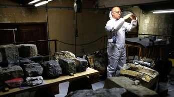 Steinexperte Jean-Didier Mertz schaut in einem Lagerhaus auf die Überreste des goldenen Engels, der einst auf der Kathedrale von Notre Dame stand.