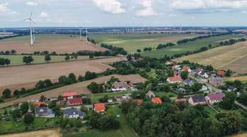 Blick auf das Dorf Carzig mit vielen Windenergieanlagen im Hintergrund. Die geplante Regelung für den Abstand von Windrädern und Wohnsiedlungen sorgt für Ärger.