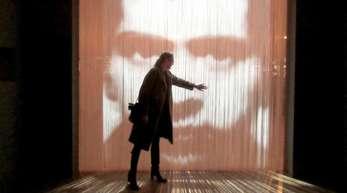 Eine Besucherin steht vor einem Kunstwerk, einem Streifenvorhang mit einem Porträt des französischen Konzeptkünstler Christian Boltanski.