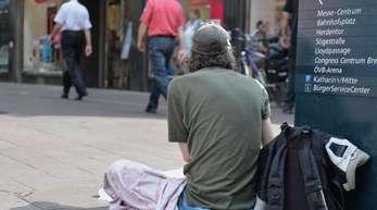 Ein Obdachloser sitzt in der Innenstadt von Bremen und bettelt. Viele Verbraucher in Deutschland sind nicht in der Lage ihre Rechnungen zu zahlen.