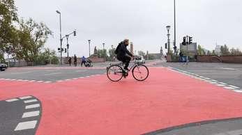 Ein Mann fährt mit einem Fahrrad auf einem rot gekennzeichneten Fahrradweg über eine Straßenkreuzung.