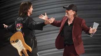 Lars Ulrich (r), Schlagzeuger und Songwriter der Band Metallica, beglückwünscht Juanes.