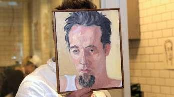 Sebastian Brecht hält sich ein Portrait vor sein Gesicht, das die Künstlerin Alix Bailey von ihm gemalt hat.