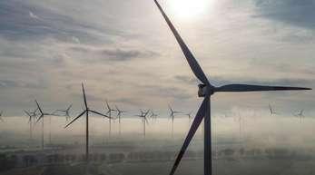 Windräder drehen sich im Morgennebel in Brandenburg.