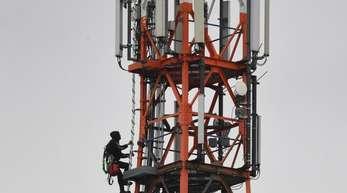 Ein Techniker klettert an einem Funkmast neben Mobilfunkantennen für den Mobilfunkstandard 5G.