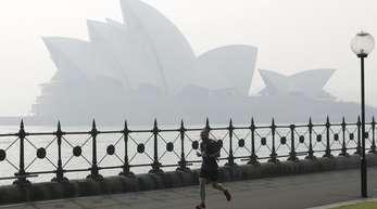 Ein Jogger läuft am Morgen, während Rauchschleier über der Sydney Opera House hängt.