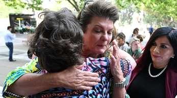 Julie Davis umarmt eine weitere Betroffene vor dem Gerichtsgebäude. Mehr als 1300 Frauen haben inAustralien eine Sammelklage gegen den US-Pharmakonzern Johnson & Johnson wegen Gesundheitsstörungen infolge fehlerhafter Scheiden-Implantate gewonnen.