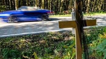 Ein Holzkreuz steht bei Achslach an der Stelle, an der die Männer bei einem Rennen den Tod eines weiteren Autofahrers verursacht haben sollen.