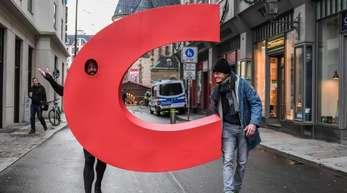 Ein Aktivist geht mit einem nachgebauten Buchstaben C aus dem Logo der CDU vor der Nikolaikirche in Leipzig über eine Straße.