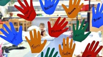 Aus Folien geschnittene Kinderhände hängen mit den jeweiligen Namen an der Eingangstür einer Kindergruppe in einer Tagesstätte.