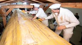 Bäcker der Schutzgemeinschaft Dresdner Stollen streichen Butter und Zucker auf den Riesenstollen.