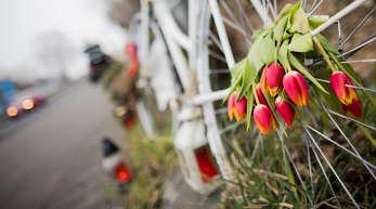 Tulpen in den Speichen eines Fahrrads erinnern am Unfallort in Köln an den Tod der 19-jährigen Radfahrerin.