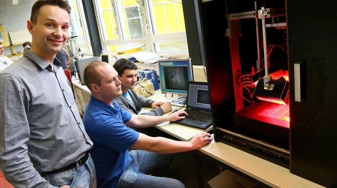 Daniel Kray (von links) durchleuchtet mit Andreas Jankowski und Samuel Meier Solar-Module.