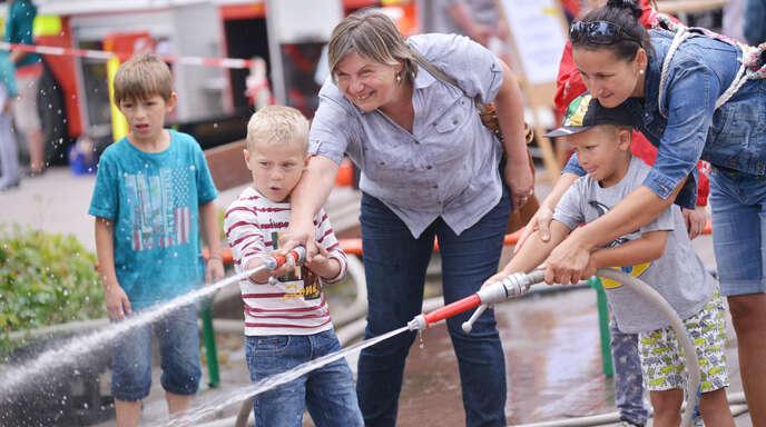 Mit Unterstützung der Mamas den spielerischen Einsatz als Feuerwehrmann üben – eine der seit Jahren beliebten Aktionen des Kindertags, organisiert von der Freiwilligen Feuerwehr.