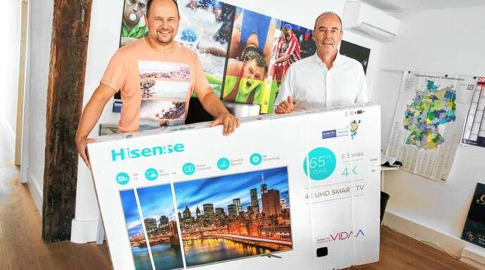 Mitmachen beim Tippspiel lohnt sich, wie man sieht: Gewinnspielleiter Marcus Hug (links) und Sportchef Rüdiger Rüber von der Mittelbadischen Presse präsentieren den Hauptgewinn – einen 65-Zoll-Fernseher.
