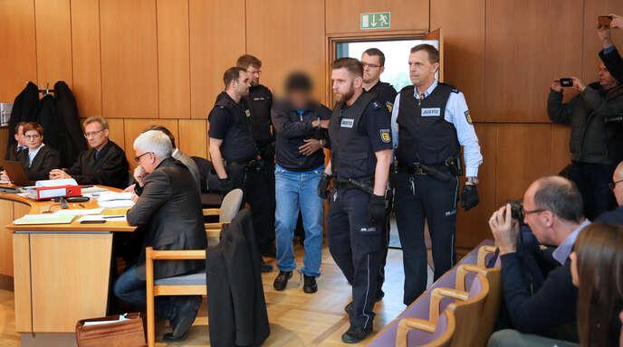Der Angeklagte wird am ersten Prozesstag in den Saal geführt. Auch am zweiten äußerte er sich nicht zur Tat.